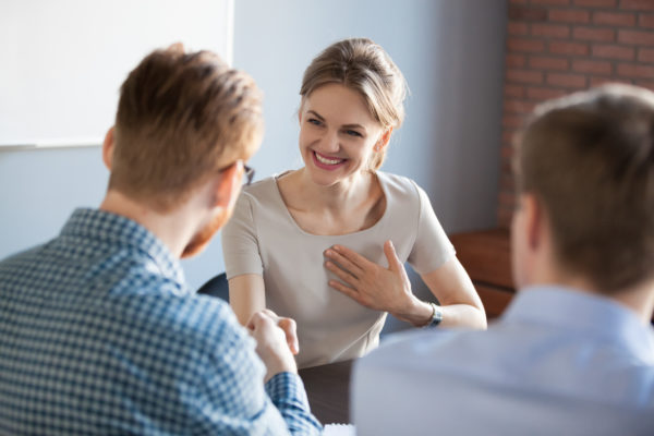Back view of male worker shaking hand of happy satisfied female colleague or partner during office meeting, businessman complimenting woman, boss handshaking employee congratulating with success